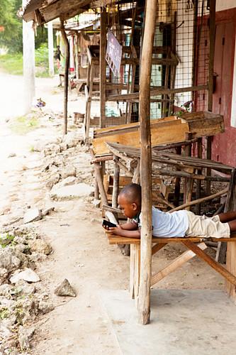 Kenyan child with smartphone, ruined city, Gede, Malindi, Kenya