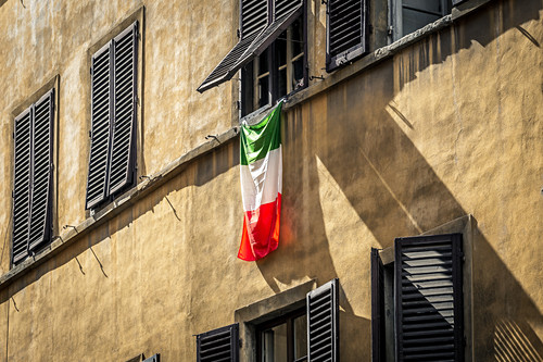 Häuserfassade mit italienischer Flagge in Florenz, Italien