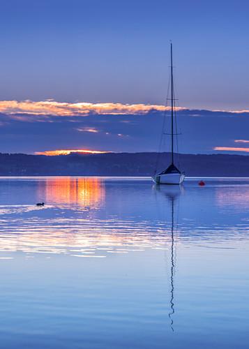 Boot im Gegenlicht bei Sonnenaufgang am Starnberger See, Tutzing, Bayern, Deutschland