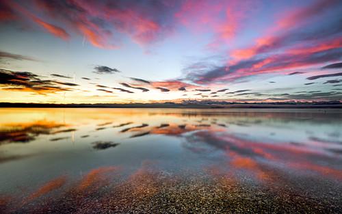 Sonnenaufgang  mit spiegelnden Wolken am Starnberger See, Bayern, Deutschland