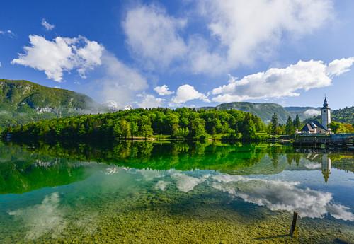 reflection at Lake Bohinj, with mountains and medieval church, Ribcev village, Stara Fuzina, Bohinj, Gorenjska, Julian Alps, Triglav National Park, Slovenia, Europe