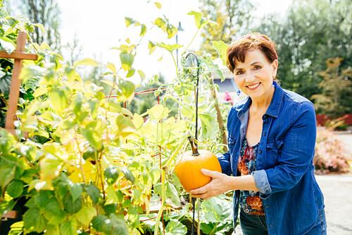 Caucasian woman holding pumpkin in garden