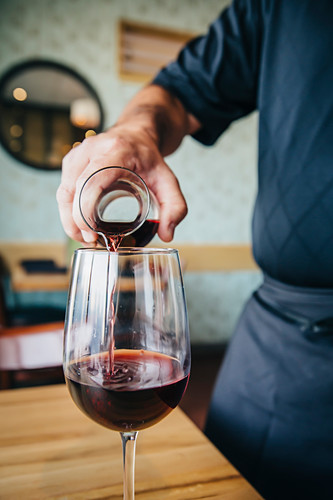 Caucasian waiter pouring wine in cafe