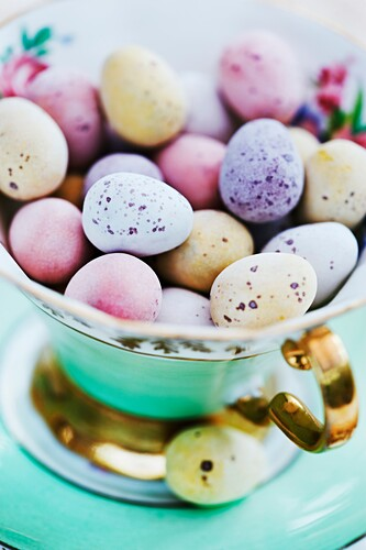 Candy coated chocolate easter eggs in antique china tea cup.