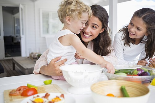 Happy young family preparing vegetables at home