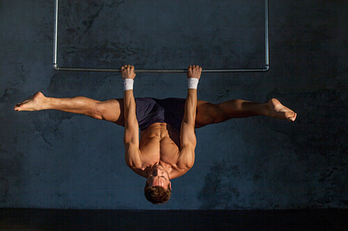 Gymnast with bare upper body doing an upside-down straddle, Germany