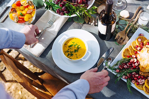 Caucasian man setting platter of soup on outdoor table
