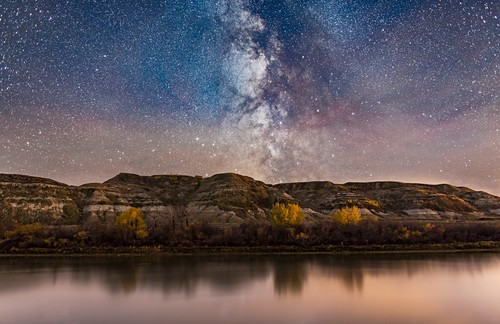 The Milky Way in Sagittarius (toward the galactic centre) going down behind the badland hills along the Red Deer River. I shot this near East Coulee on Highway 10 in Alberta, on an autumn night. Some clouds were drifting through over the exposure times. P