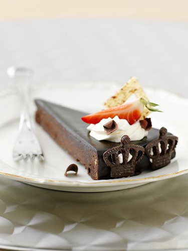 A slice of chocolate cake with cream and strawberries