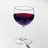 A glass of red wine against a light background