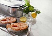 Two salmon steaks in front of a fish kettle
