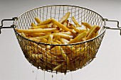 French Fries in Basket Lifted from the Fryer