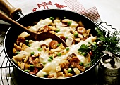 Pan-Fried Stew with Potatoes, Sausage, Peas and Melted Cheese