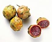 Drei ganze & eine halbierte Pitahaya mit rotem Fruchtfleisch