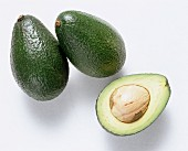 Two whole avocados and half an avocado with stone