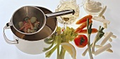 Vegetable stew ingredients; strainer with vegetables over pan