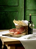 Still life with asparagus, ham and white wine