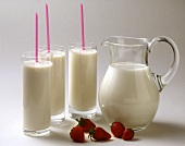 Three glasses of milk with straws; milk jug; strawberries