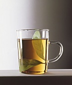 A glass of tea with a fresh bay leaf