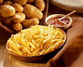 French Fries in a Bowl shown with Uncooked Whole Potatoes