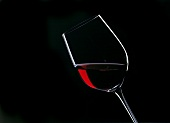 Tipped Glass of Red Wine; Black Background