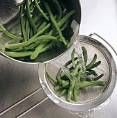 Straining blanched green beans through a sieve