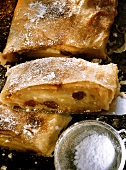 Apple strudel with icing sugar on a baking tray