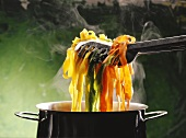 Pasta Tong Lifting Assorted Tagliatelle Out of a Steaming Pot