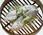 Two halibut cutlets on fennel in steaming basket
