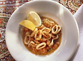 Braised squid in tomato broth with lemon wedges