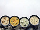 Assorted Cream Soups including Potato, Carrot with Sesame Seeds, Herb with Cream Garnish and Veal with Okra Pod Slices