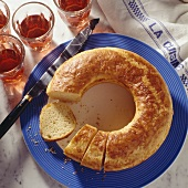Baked Cheese Brioche in Ring Form, partially sliced, on blue Plate