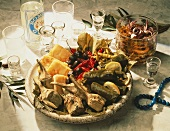 Several Greek Appetizers on Plate, Bowl with pickled Squid and Bottle of Ouzo with Glasses