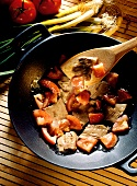 Beef and Tomatoes Cooking in a Wok; Spatula