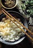 Ein Schälchen Reis auf chinesische Art gekocht, Stäbchen u.a.