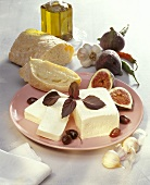 Piece of feta on plate with figs, olives & white bread