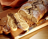 Nut plait sprinkled with icing sugar, pieces cut on wooden board