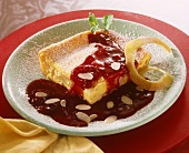 A piece of lemon cake with plum sauce & powdered sugar