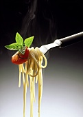 Cooked spaghetti with tomato quarter and fresh basil