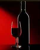 Outline of glass & bottle of red wine against dark background