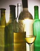 Several wine bottles, white wine bottle, glass of white wine