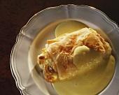 Piece of cream strudel with custard on plate