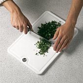 Chopping flat leaf parsley with knife on white chopping board