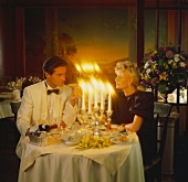 A Man and Woman Having Dinner by Candle Light