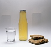 Glass of mineral water, bottle of bread drink & bread slices
