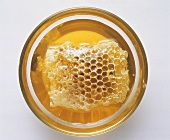 A small bowl of honey with honeycomb