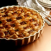 Linzer tart in baking tin; cake forks, plate, tablecloth