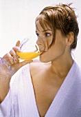 Junge Frau im Bademantel trinkt Orangensaft aus Glaskelch