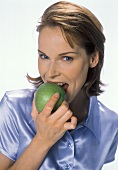 Young woman biting into a green apple (Granny Smith)
