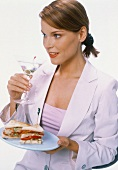 Young woman in white blazer with martini glass & sandwiches